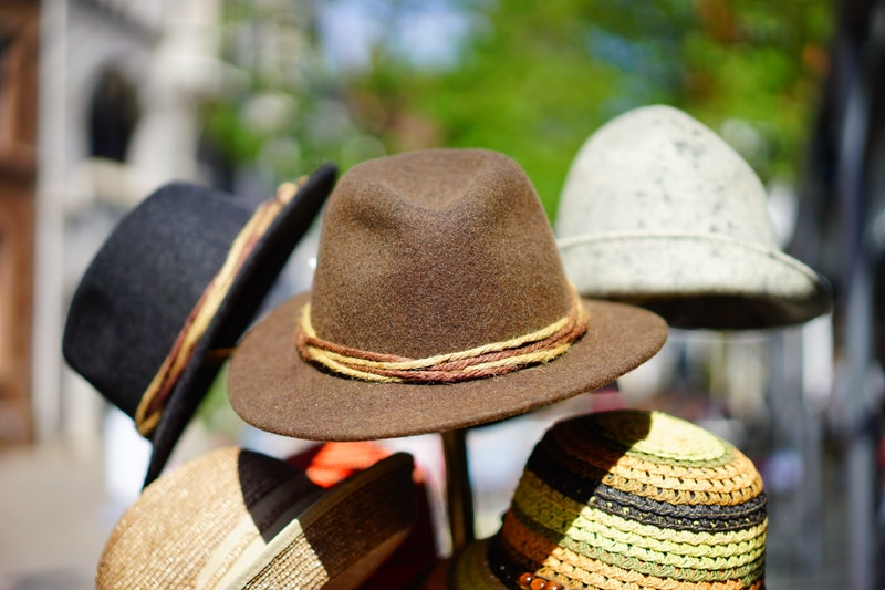 At least five different hats of varying colours sit on a hat stand outside.