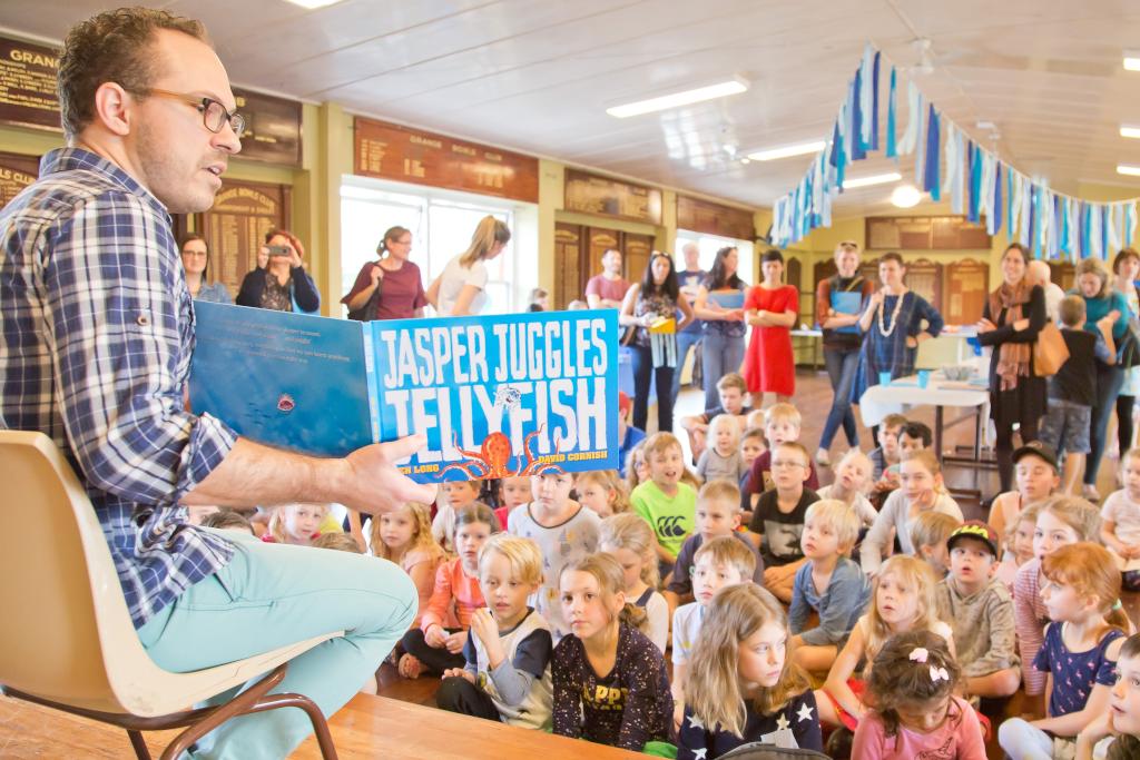 Ben reads Jasper Juggles Jellyfish to a group of children.