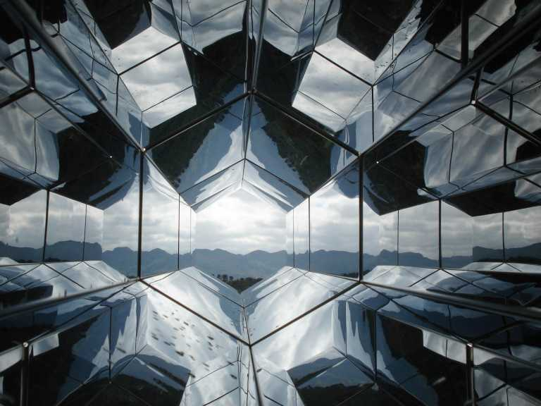A futuristic looking world reflected by hexagonal mirrors