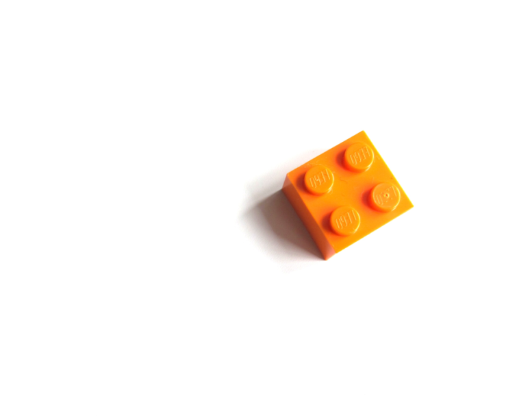 Single orange 2x2 LEGO brick with shadow on white background.