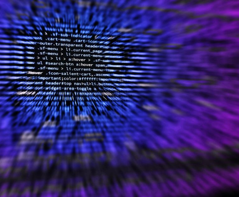 Blurred code on a screen in shades of blue and purple.