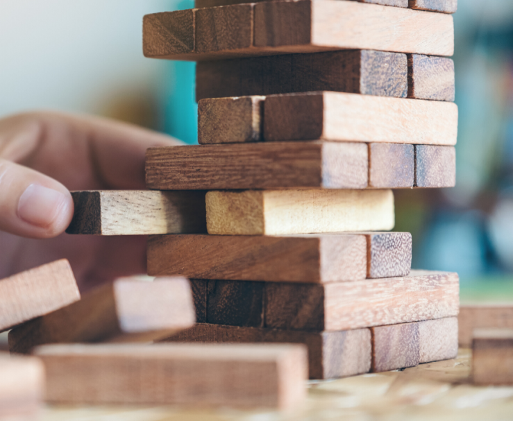 A hand is seen carefully pulling a wooden block from the middle of a tower, as part of a block stacking game.