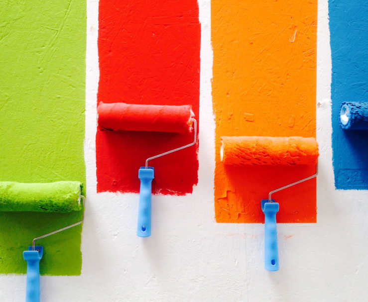 Four paint rollers, each used to paint a different colored stripe on a white wall - green, red, orange, and blue.