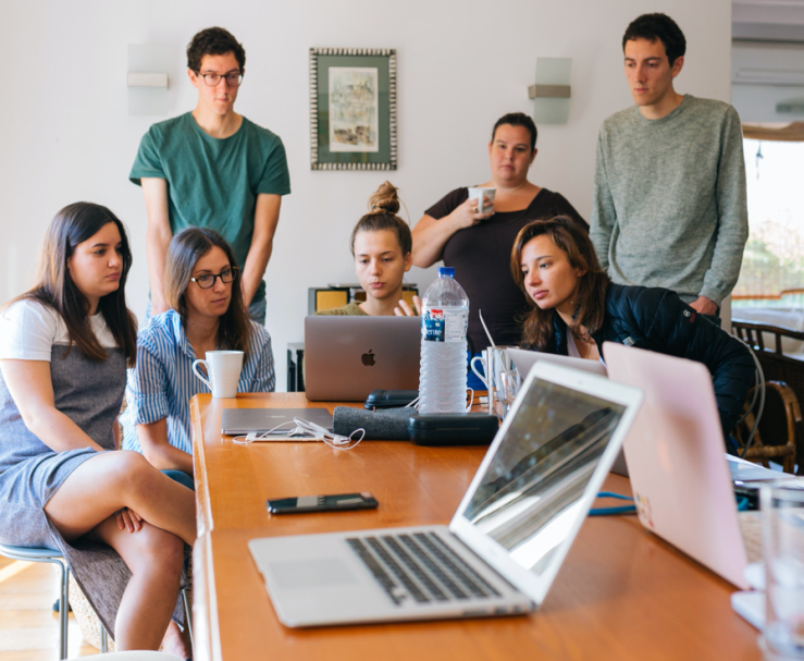 A group of eight young adults crowd around a laptop.