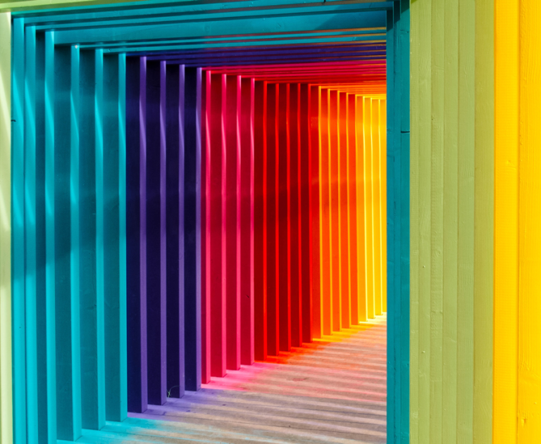 A brightly coloured corridor lined with rainbow-colored wooden arches.