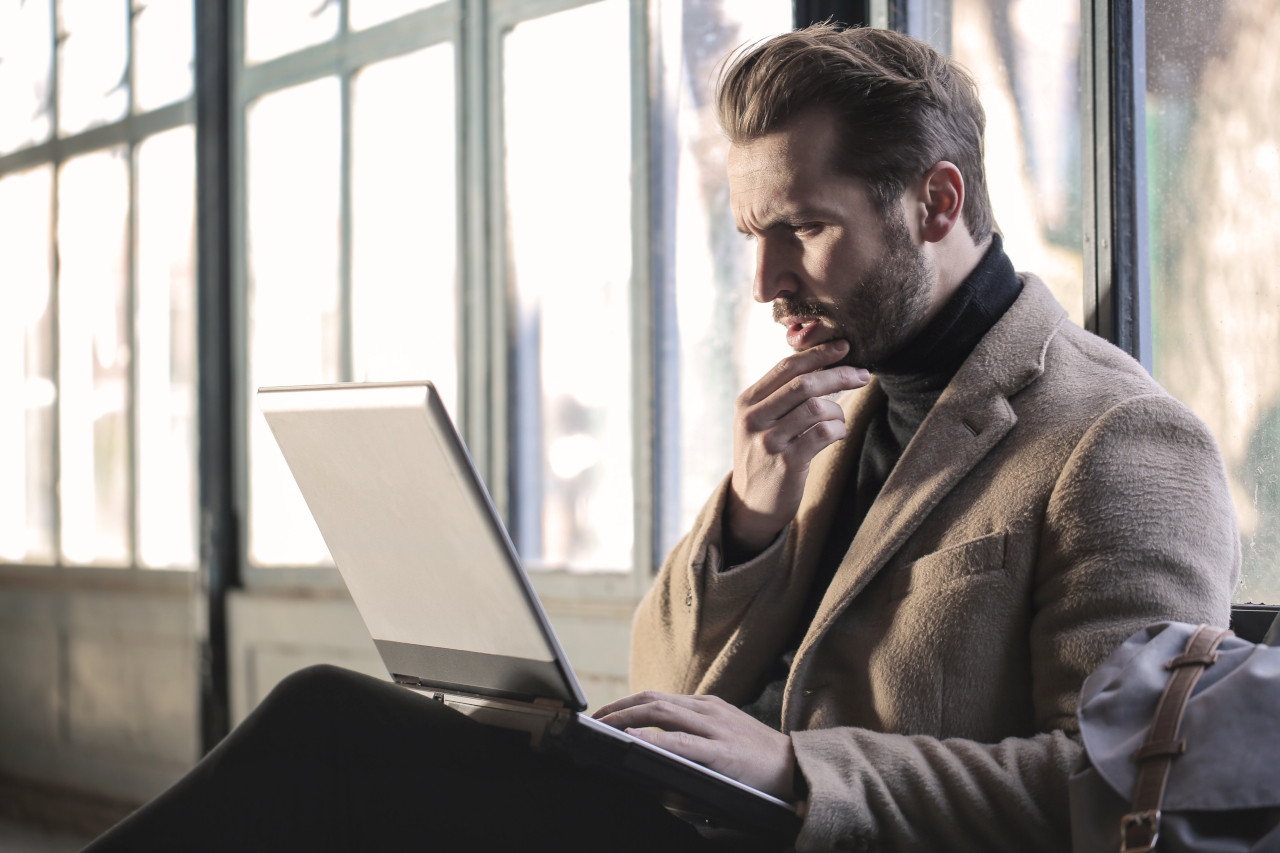 Bearded man in brown coat looks quizzically at his laptop.
