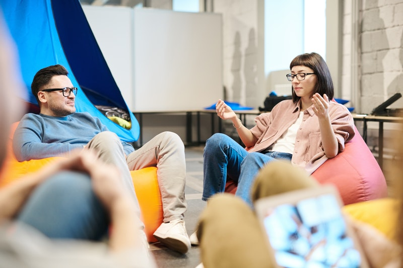 A group of people sitting on bean bags discuss ideas. A man and woman are visible