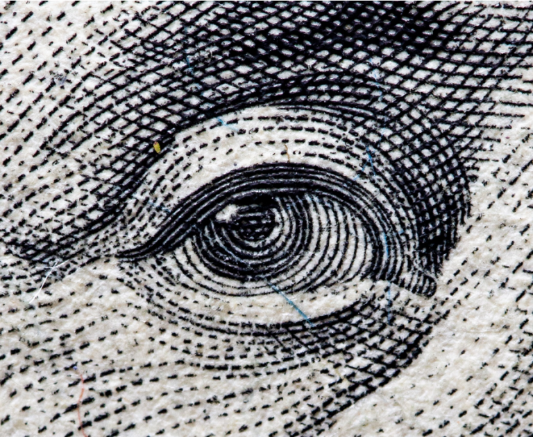 Cropped eye of a person printed on a cash note.