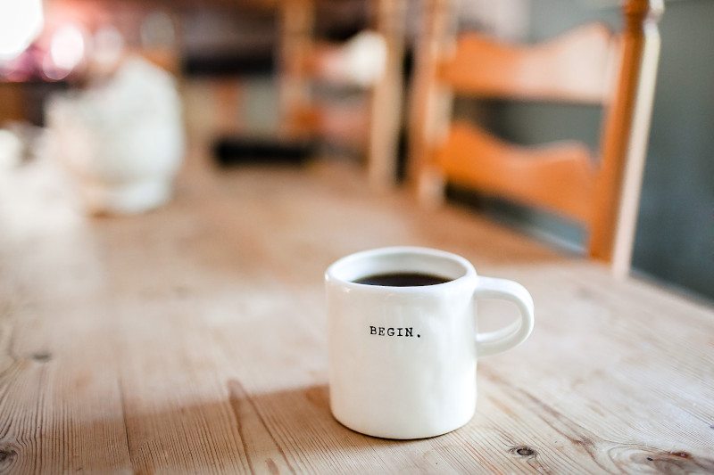 "A motivational coffee mug printed with the word ""begin"" sits on a wooden table."