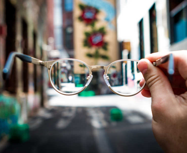 A person holds up a pair of glasses while in an urban setting, with just their hand visible in the image.