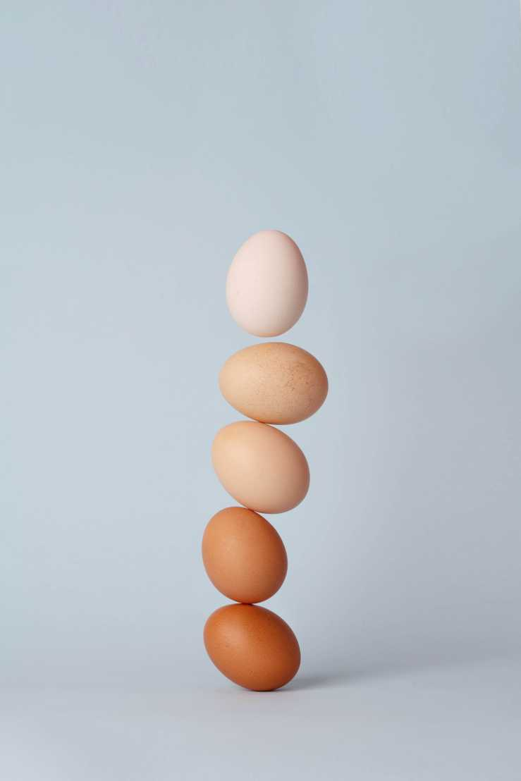 Five eggs are stacked precariously on top of each other.