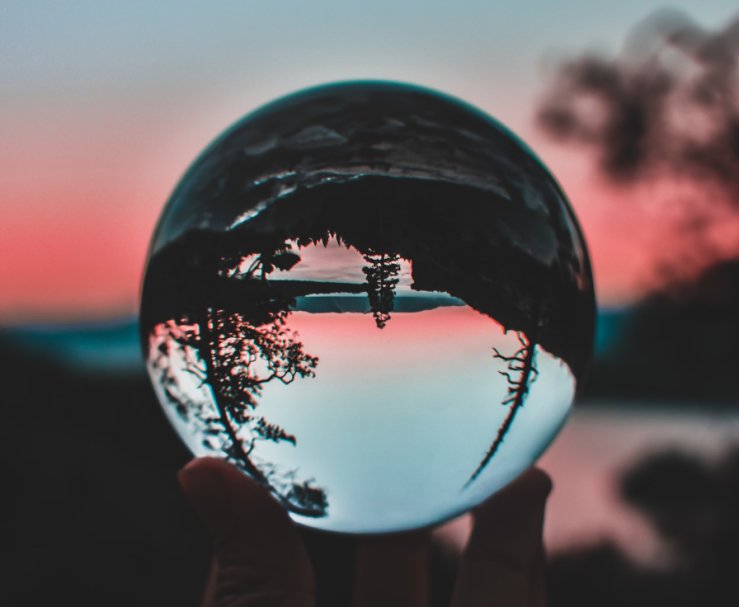 Glass ball displaying inverted image of trees and sunset behind.