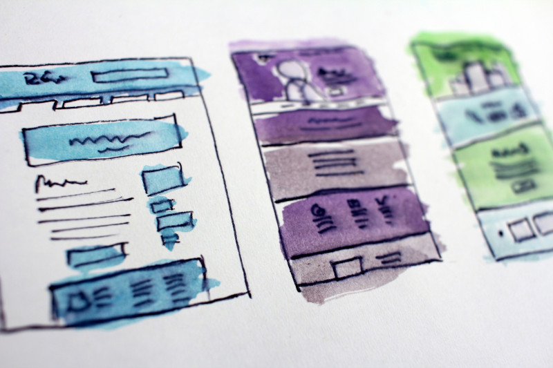 Hand drawn mockups show 3 different screens of a web app or website. Headers, images, and sections are planned out using boxes or colored highlighters.