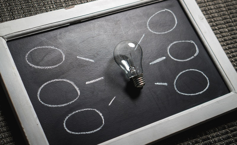 A lightbulb rests on top of a black chalkboard with 6 circles drawn in white chalk