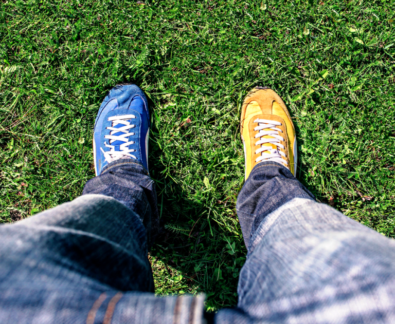 Person stands on the grass, wearing dark blue jeans with one blue and one yellow shoe.