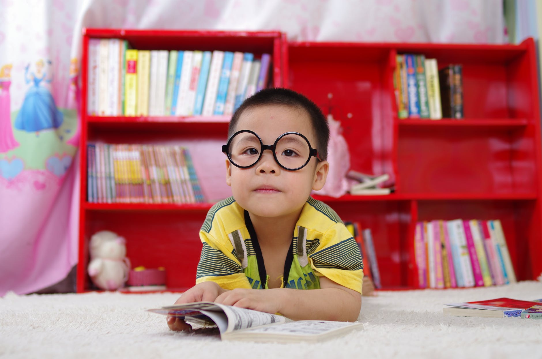 Young boy wearing glasses and reading a book