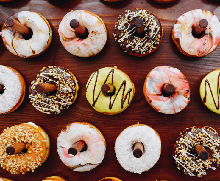 An assortment of decorated donuts are displayed on a wooden donut board.