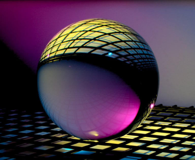 A crystal ball on top of illuminated squares.