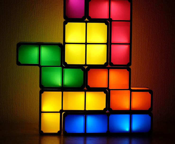 Illuminated 3D Tetris blocks, in different colors, stacked together.