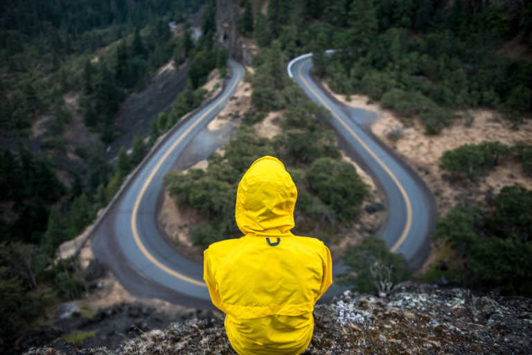 Person in yellow raincoat looking at road that goes in two different directions.