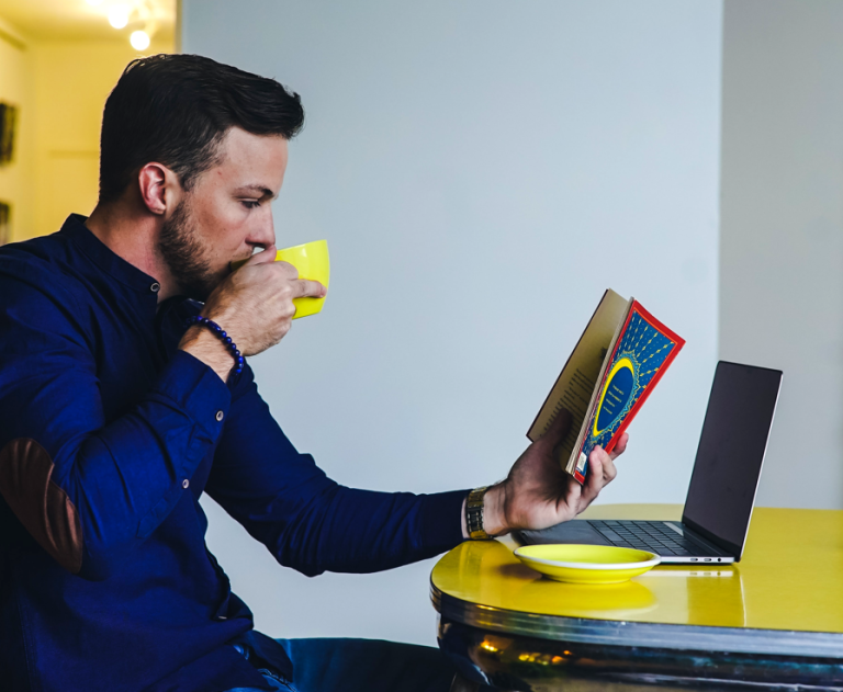 Man sips a hot beverage from a yellow teacup, while sitting in front of an open laptop on a yellow table and reading a book.
