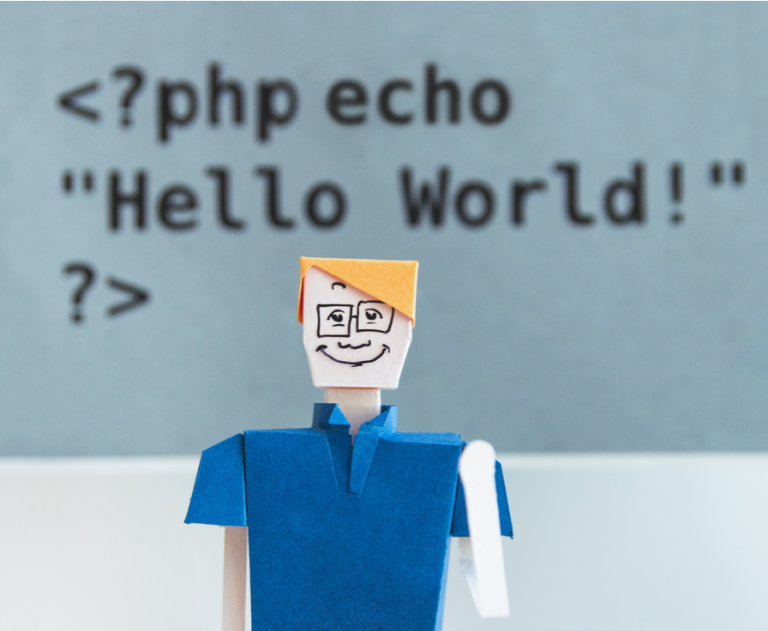 "Origami in the shape of a man waving, in front of a background with code <?php echo ""Hello World!""?>."