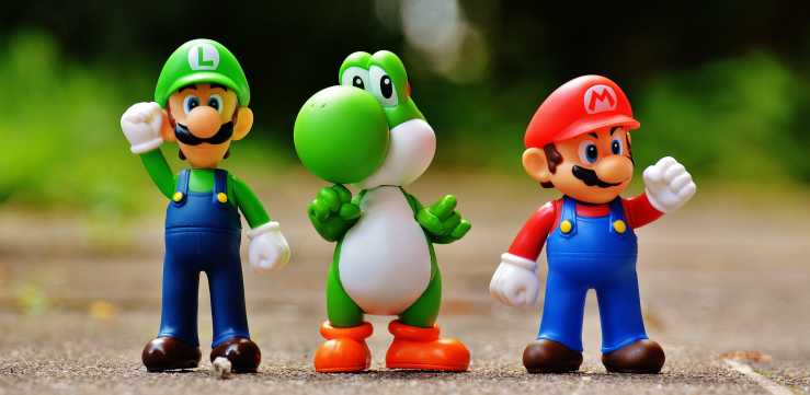 Super Mario, Luigi, and Yoshi figurines standing together on a hard surface.