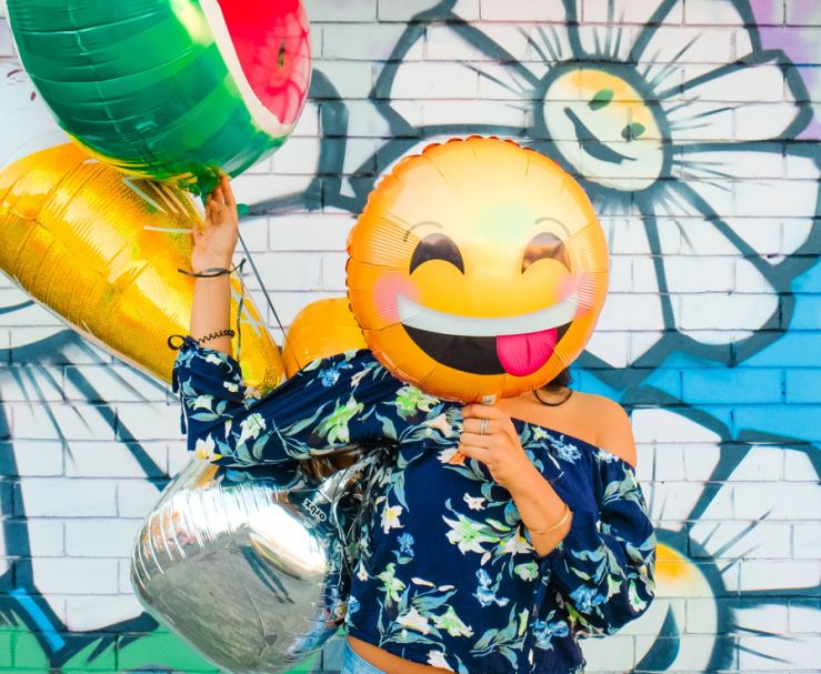 Woman stands in front of a colorful painted brick wall, holding balloons shaped like emoji, with a cheeky-faced balloon covering her face.