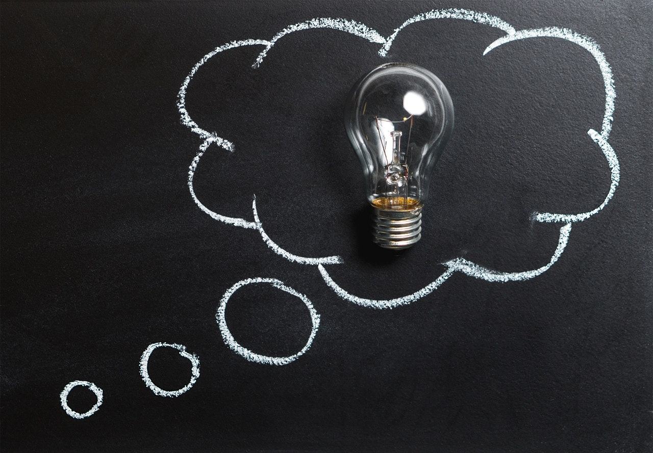 A lightbulb resting on a blackboard inside a thought bubble drawn in white chalk.
