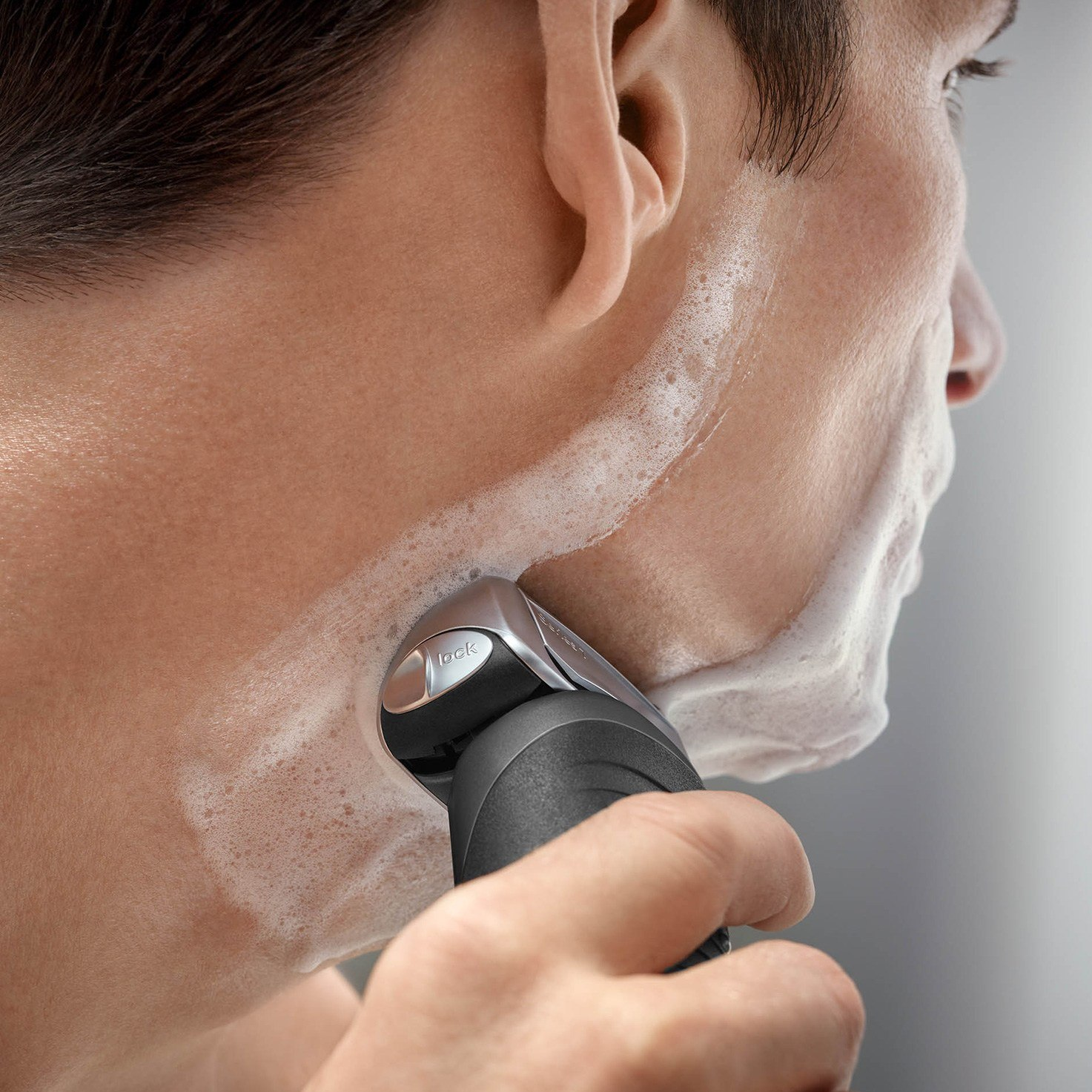 Braun Series 7 grey electric shaver in use
