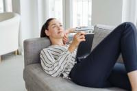 Eine Frau mit einem iPad auf der Couch