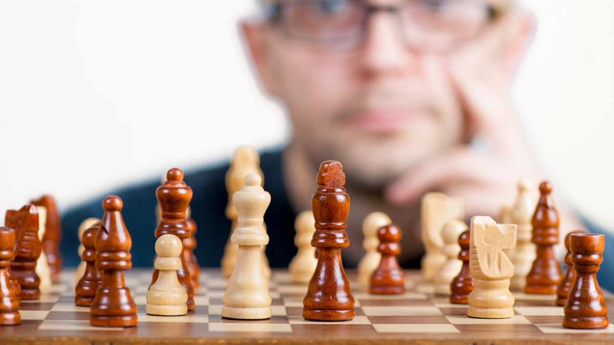 Chess board, with man's face blurred in the background