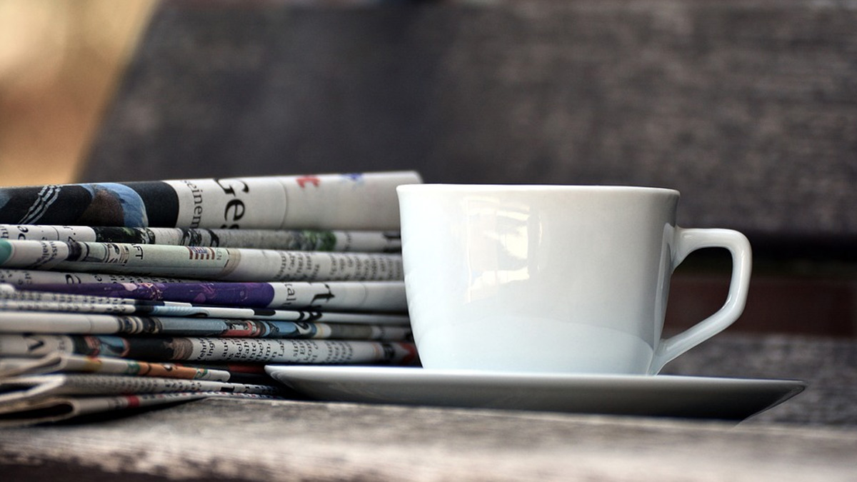 Newspapers stacked on surface next to a mug and saucer