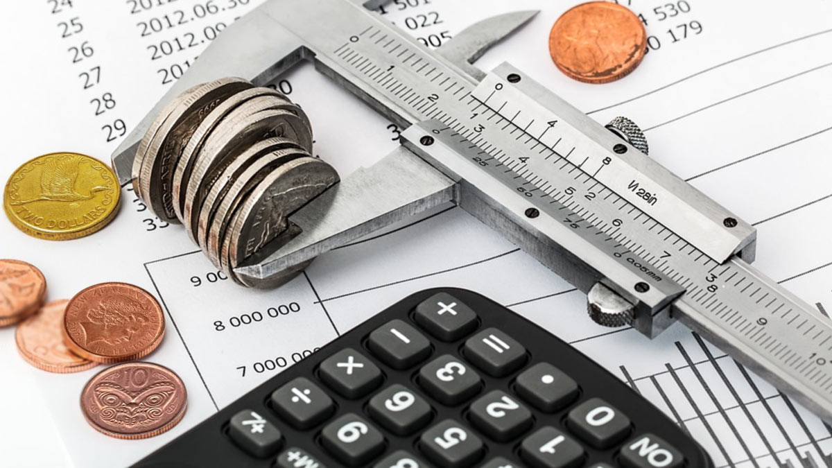 Coins, calculator and ruler sitting on piece of paper with figures on it