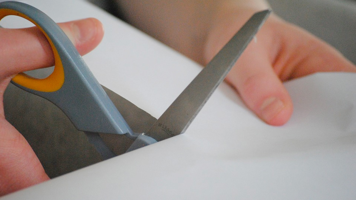 Hands cutting white paper with scissors