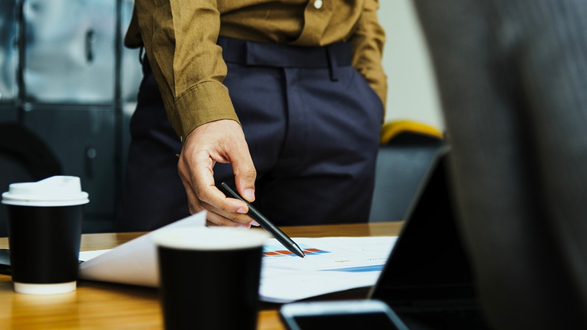 Corporate male holding pen, pointing with pen to graph on table