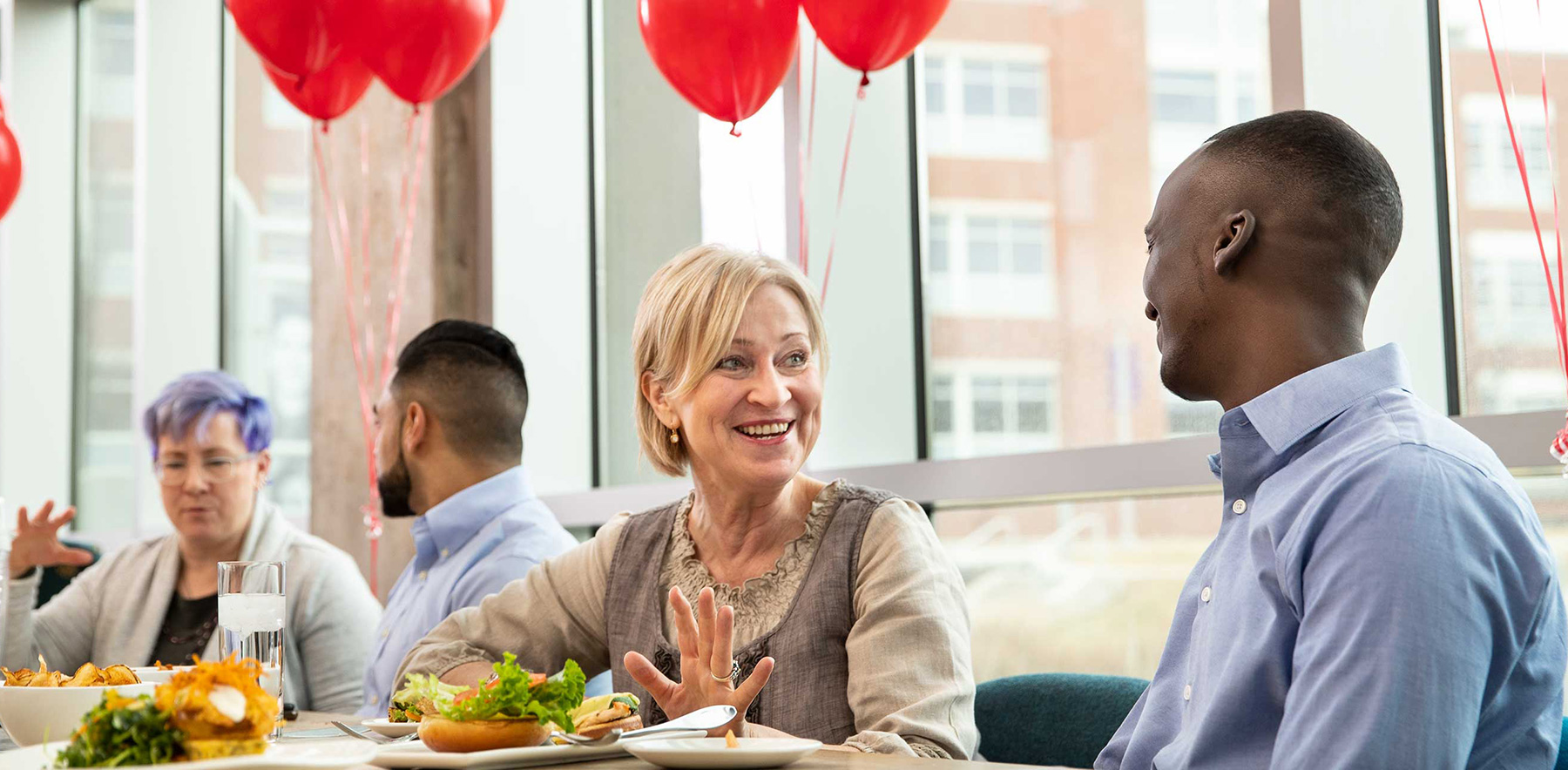 people talking at the table of a team building lunch with red balloons