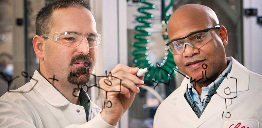 两位科学家在玻璃板上写方程