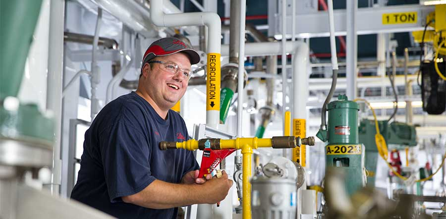 man smiling and holding lever in manufacturing