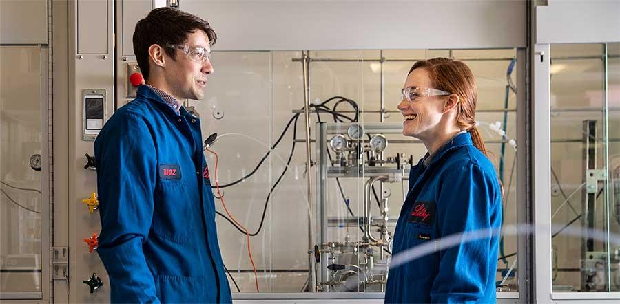 年轻的男人和女人在实验室齿轮说话