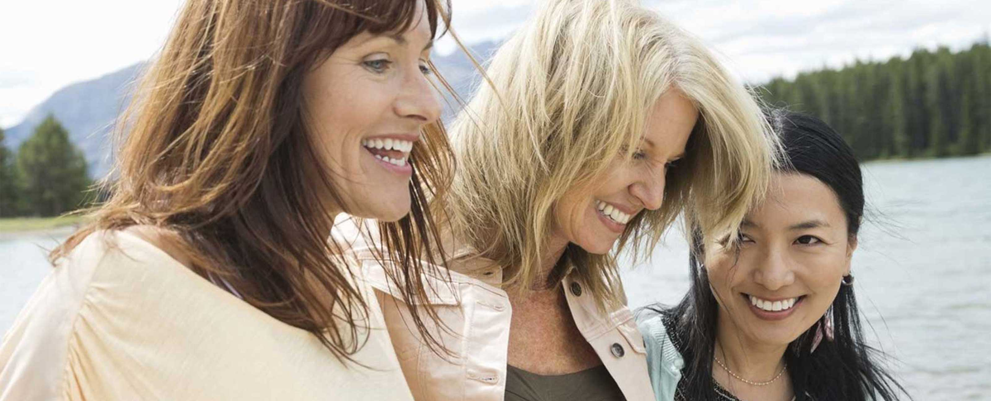 three women laughing by lake legacy image