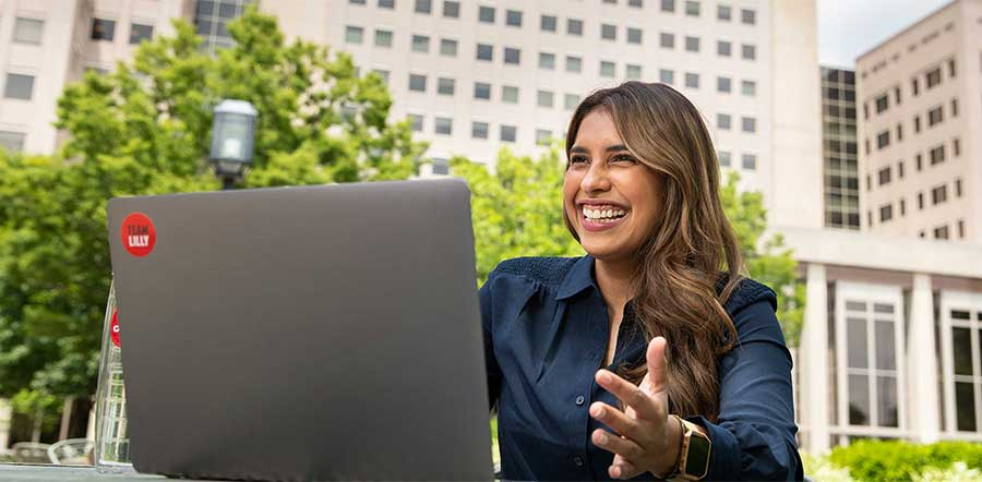 woman smiling outside lilly corporate center working on laptop