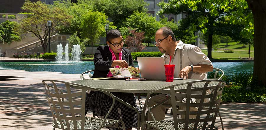 two people working at table outside in front of fountain