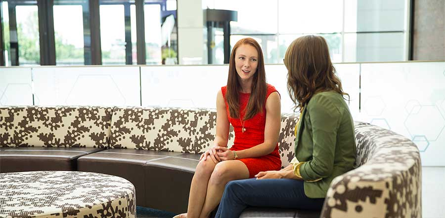 two women talking in a lobby sitting on a couch