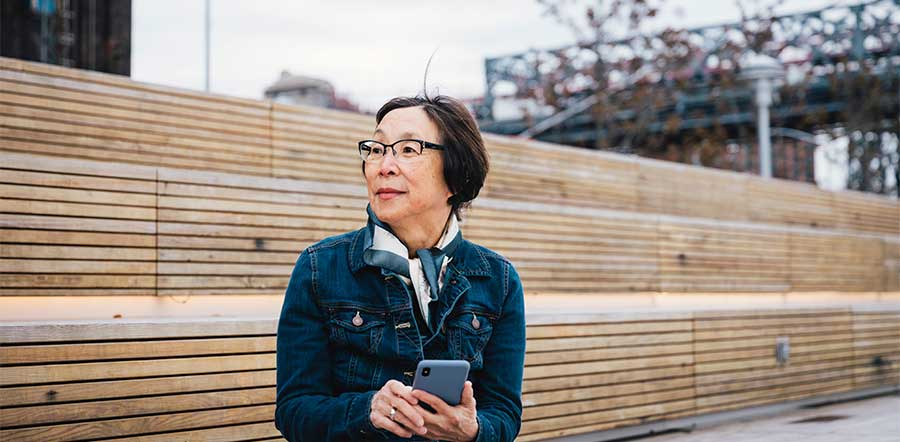 woman sitting outside holding smartphone