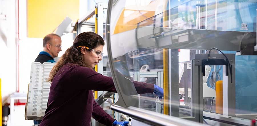 woman working in manufacturing reaching hand inside glass case