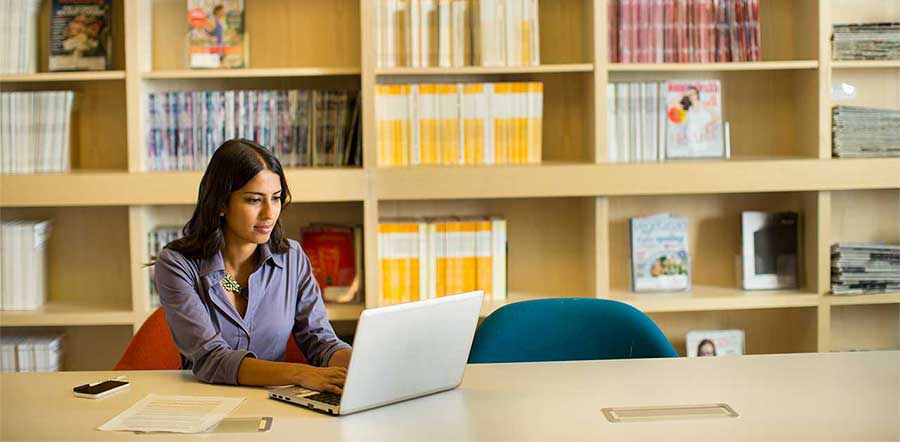 woman working on laptop sitting in library