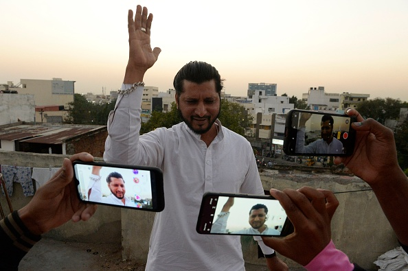 An artist acts in front of a mobile phone camera while making a TikTok video on the terrace of his residence in Hyderabad on February 14, 2020 (NOAH SEELAM / AFP via Getty Images)