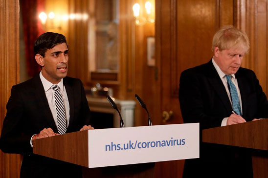 Britain's Chancellor of the Exchequer Rishi Sunak (left) speaks beside Prime Minister Boris Johnson at a news conference addressing the government's response to the COVID-19 outbreak, on March 17, 2020. (Matt Dunham/Pool/AFP via Getty Images)