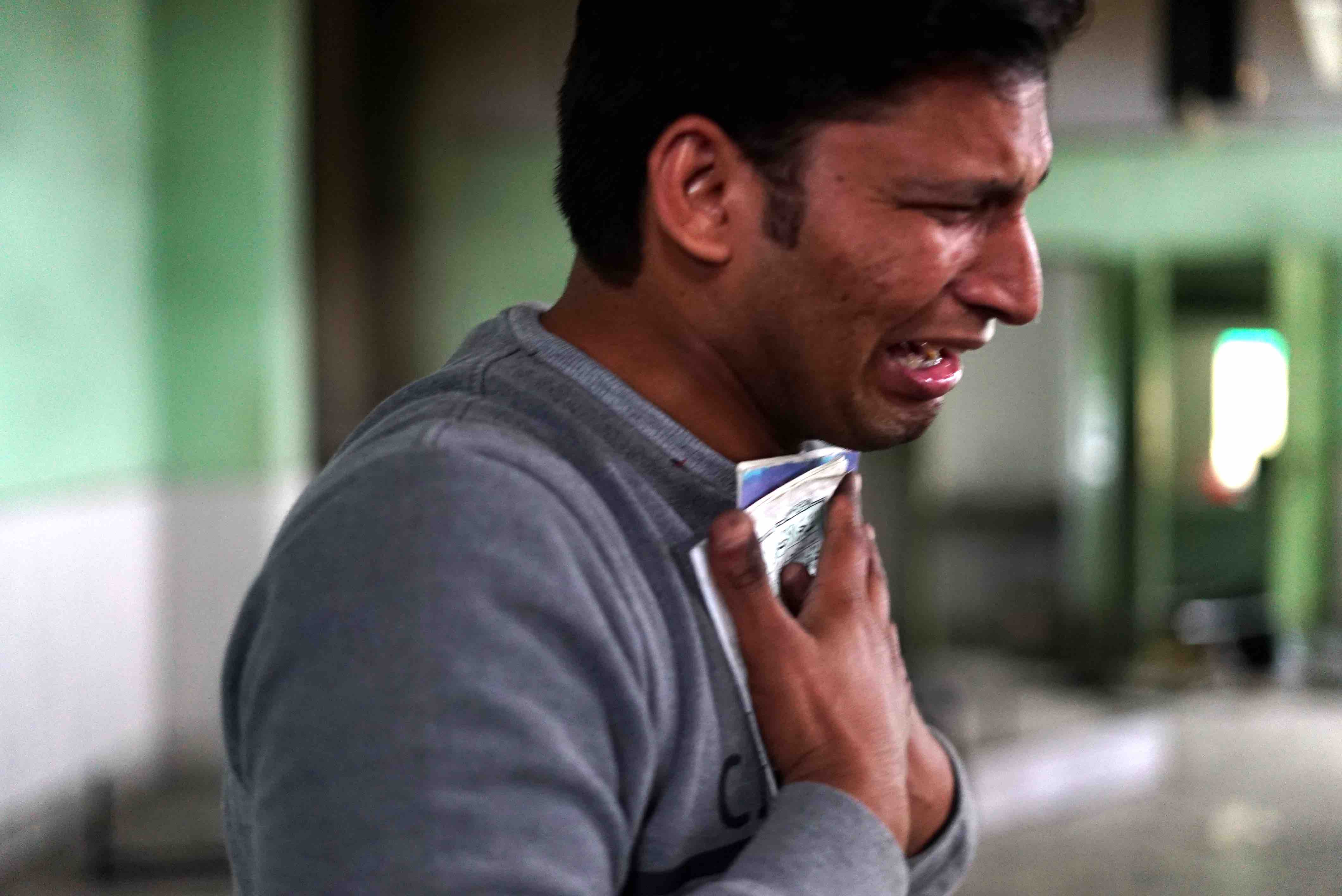 Yakub Pathan, age 24, weeps as he gathers loose pages from the Quran inside his desecrated mosque. Pathan is a barber, but his shop was burned down a week ago in the riots in Dehli's northeast. (Erin Blair)